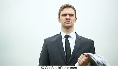 businessman standing with a stack of paper in the wind holds...
