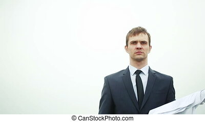 businessman standing with a stack of paper in the wind....