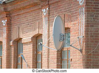 Satellite dish on a brick wall.