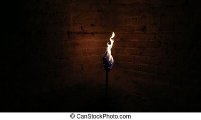 Torch light in the dark - Blazing torch next to a brick wall