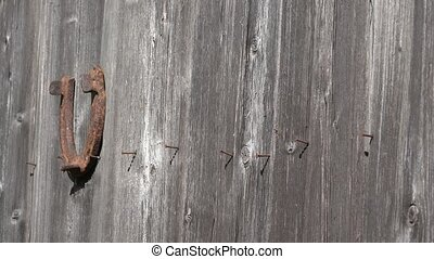 Country woman hand hang old rusty horseshoes on old wooden door - symbol of luck. 4K