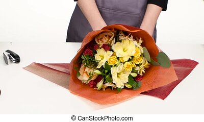 Hands female florist make up the composition of flowers....
