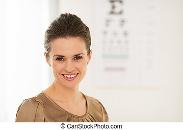 Happy young woman in front of Snellen chart - Modern health...