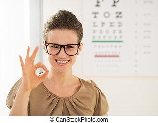woman wearing eyeglasses showing ok gesture near Snellen...
