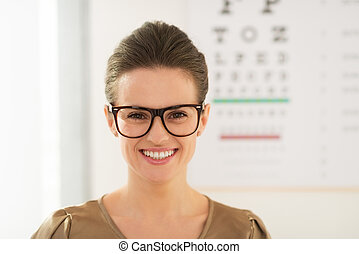 Smiling young woman wearing eyeglasses in front of Snellen...