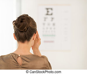 Seen from behind woman testing vision with Snellen chart -...