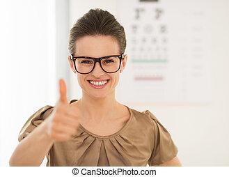 Woman wearing eyeglasses showing thumbs up near Snellen...