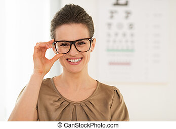 Happy young woman wearing eyeglasses in front of Snellen...