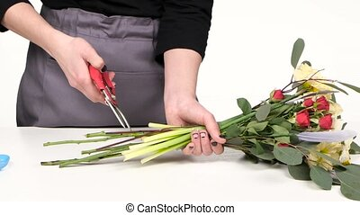 Lady is cutting flower stems. White. Close up - Florist...