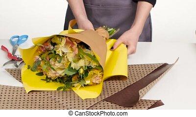 Packing bouquet. Florist wraps a bouquet of paper. White....