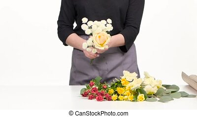 Florist assemble a bouquet. White. Close up - Woman assemble...