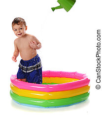 Fun Getting Wet - A happy toddler in a kiddie pool getting...