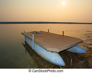 Pontoon morning - Dawn over a lake in Canada with a pontoon...