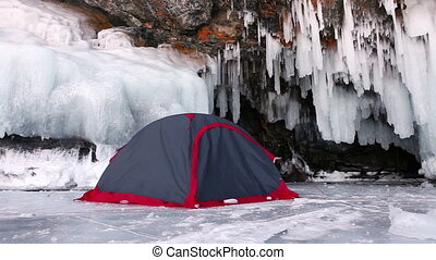 Camping on ice of Baikal lake - Tent close to frozen cave....
