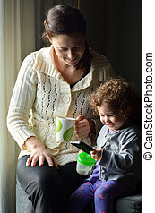 Mother and child play on mobile phone