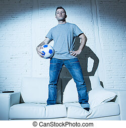 attractive man standing on top home sofa couch holding ball...