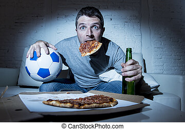 football fan man watching soccer game on tv at home sofa couch with soccer ball and pizza in his mouth