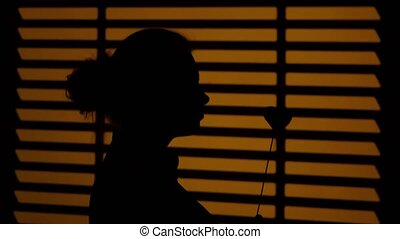 Girl standing at the window. Silhouette. Close up