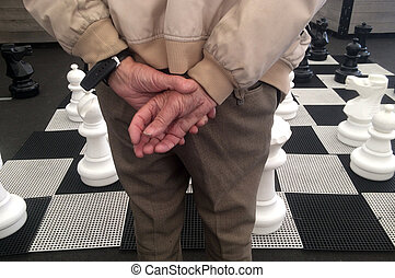 Hands of an 0ld man play giant street chess.Some...