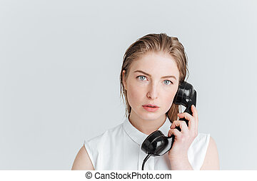 Young woman talking on retro tube isolated on a white...