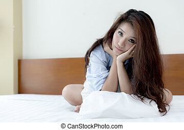 Younr Asian woman sitting on the bed looking at camera