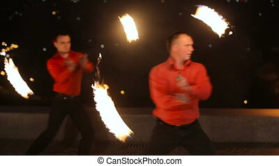 Fire show in the dark - Men and women twist fiery circles on...