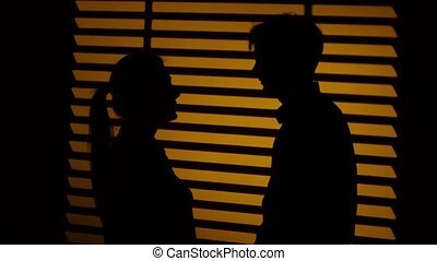 Man gives the woman a decorative heart. Silhouette. Close up...