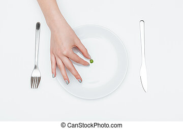 One green pea on the plate taken by woman hand - Top view of...