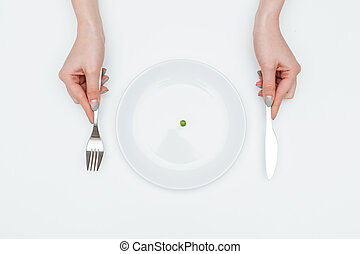 Woman eating one small green pea using knife and fork -...