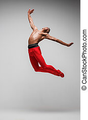 Young and stylish modern ballet dancer on gray background -...