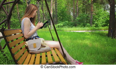 Young girl on a swing, reads the tablet pc