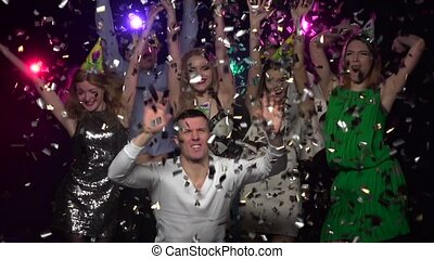 Company of friends dancing under glitter confetti. Slow...