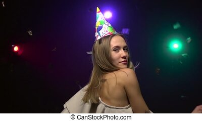 Close-up of dancing girl in party hats. Slow motion -...