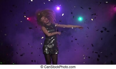 Blonde girl dancing and whirling under glitter confetti....
