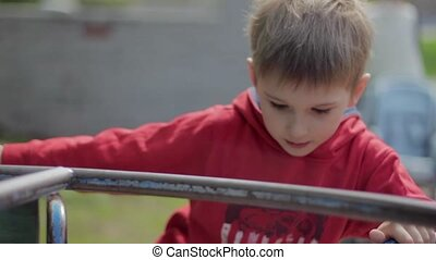 Boy on merry-go-round in park. Carousel. Slowmotion