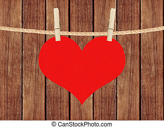 red heart hang on clothespins over wooden planks background