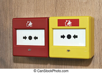 Close up of a fire alarm system on a wood panel