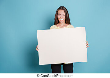 Pretty young woman holding empty blank board over blue...