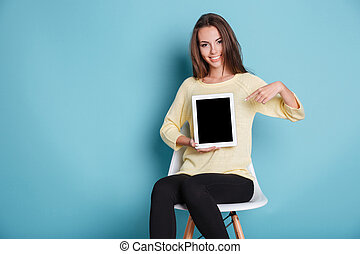 Smiling girl pointing finger at the blank screen - Beautiful...