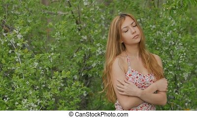 blonde girl on a background of flowering trees - beautiful...