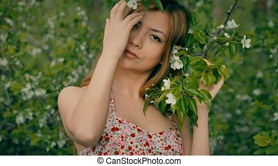 girl holds a blossoming apple tree branch - young blonde...