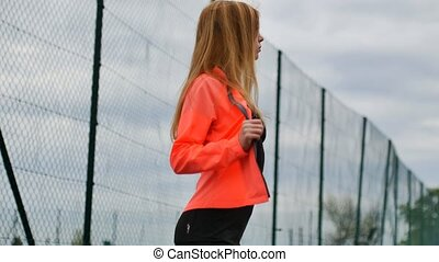 girl sportswoman removes his jacket on video - blonde girl...