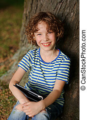 The cheerful boy sits under a tree with tablet on lap and...