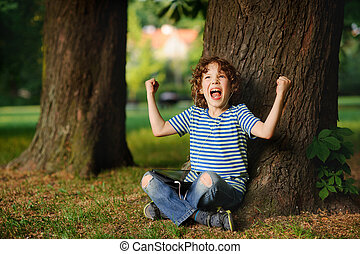 The indignant boy sits under a tree with tablet on lap. He...