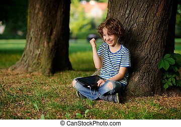 The boy of 8-9 years sits, leaning against tree and holds...