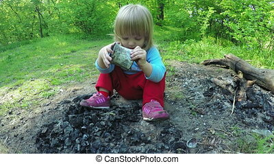 Baby on fireplace nature - Girl child playing coals on fire...