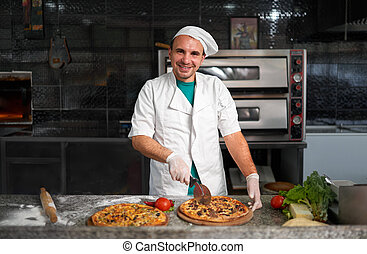 Chef cuts freshly prepared pizza on a wooden substrate. -...