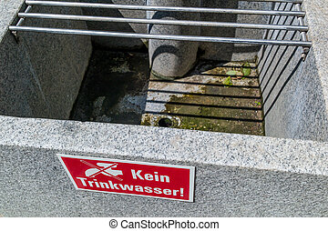 warning sign at a fountain: no drinking - in an empty well...