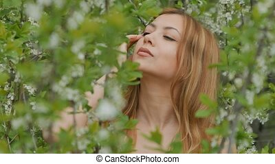 girl closes her eyes among flowering branches - smiling...