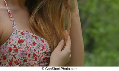 Girl corrects a dress and hair close up in the forest -...